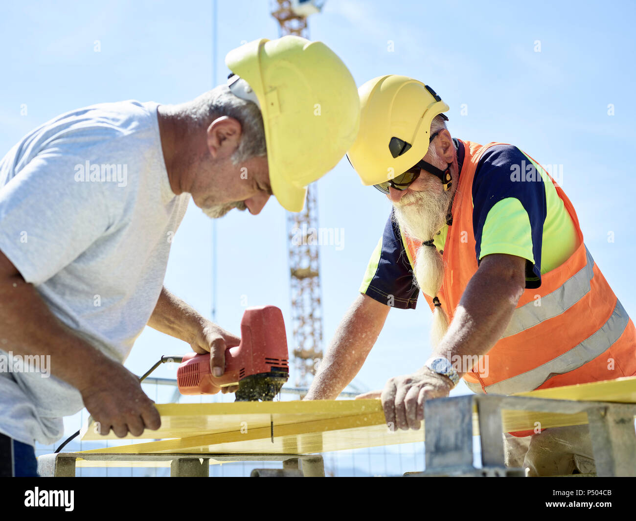 Construction worker cutting plywood with jigsaw on construction site - Stock Image