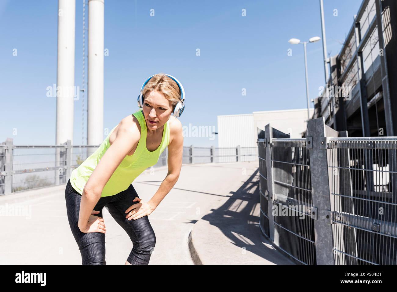 Woman jogging in the city, taking a break Stock Photo
