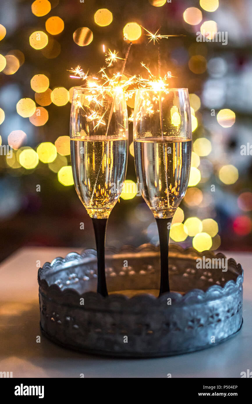Two champagne glasses and sparklers in front of Bokeh - Stock Image
