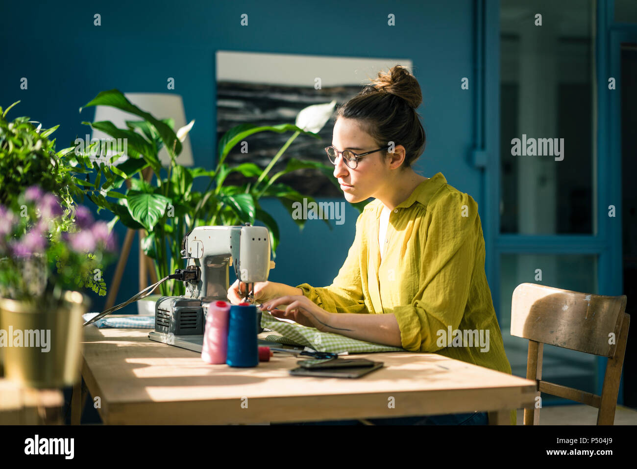 Fashion designer working with sewing machine in her studio - Stock Image