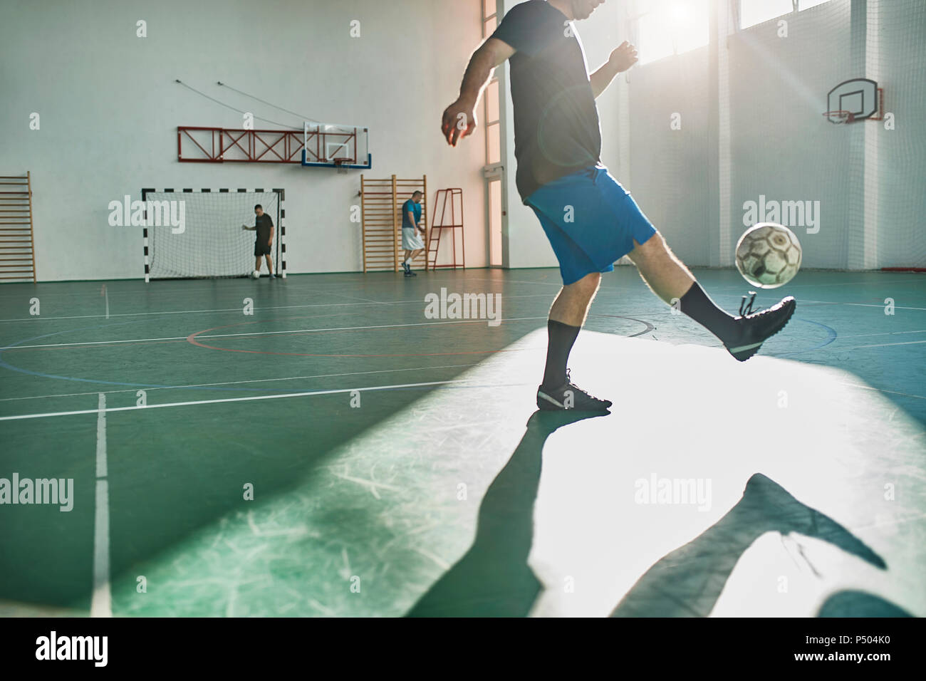 Indoor soccer player balancing the ball - Stock Image