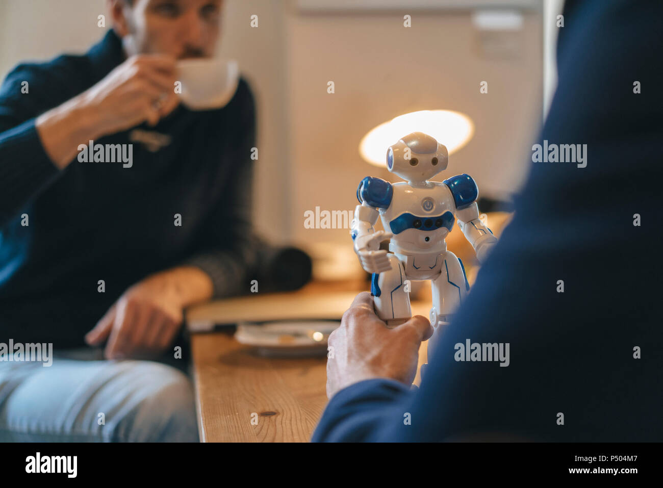 Two men and robot on table - Stock Image
