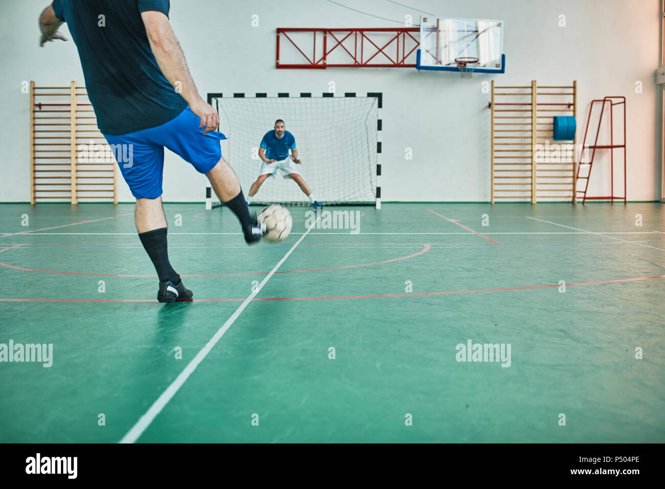 Two men playing indoor soccer shooting at goal - Stock Image