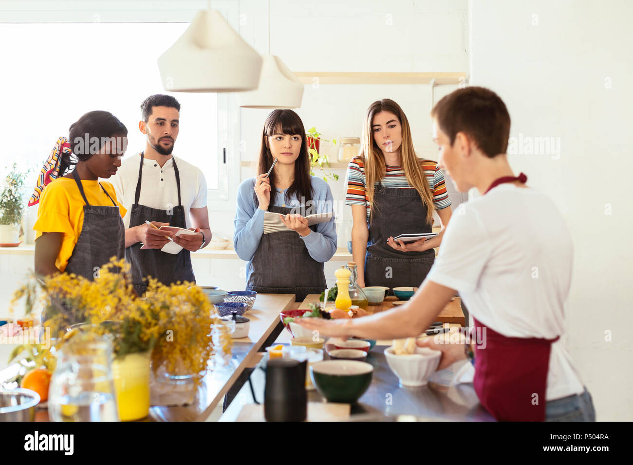 Friends in a cooking workshop listening to instructor - Stock Image