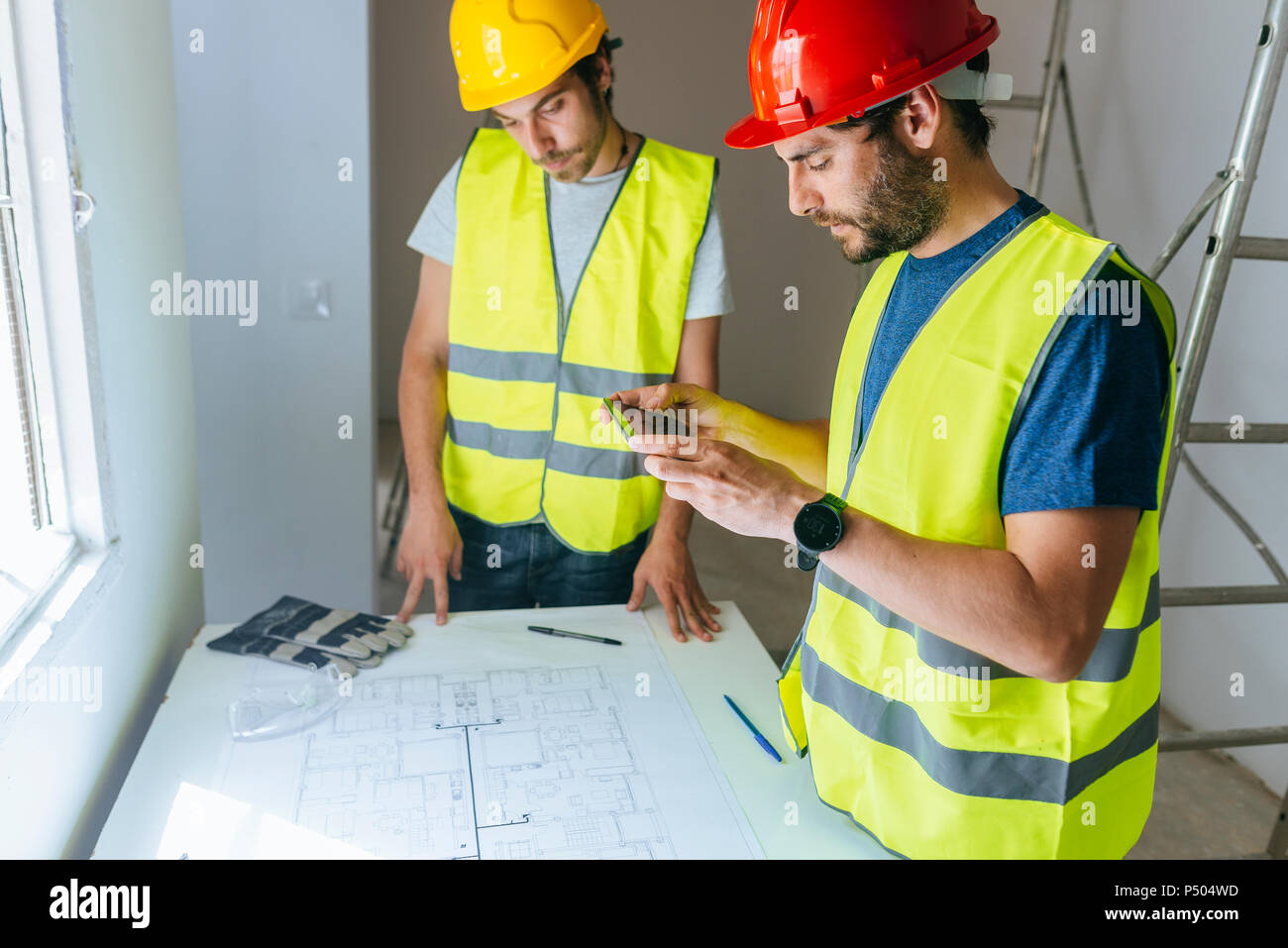 Workers taking a picture of the plan with mobile phone - Stock Image