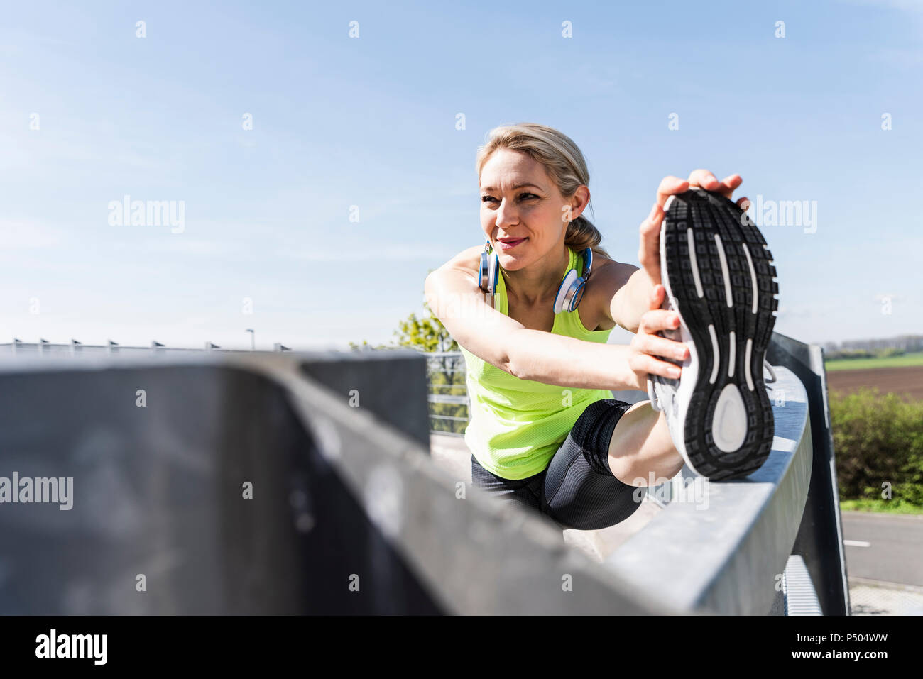 Woman jogging in the city, taking a break, stretching Stock Photo
