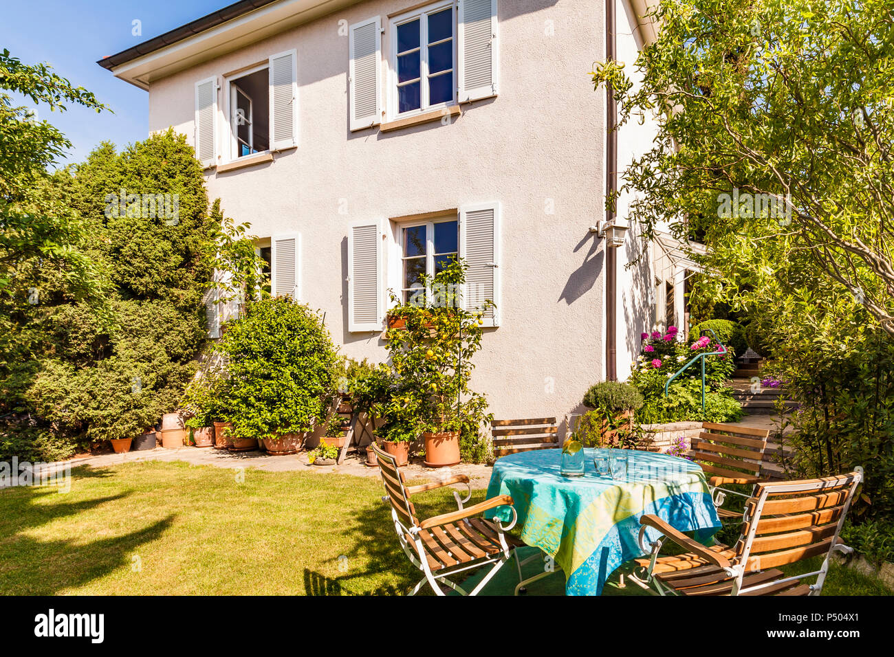 Germany, Stuttgart, one-family house, garden table with lawn chairs - Stock Image
