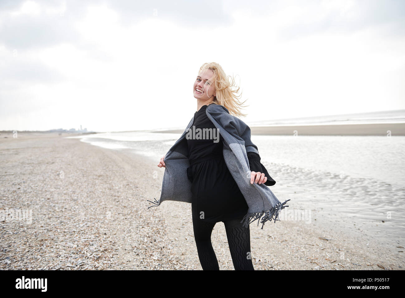 Netherlands, portrait of blond young woman running on the beach - Stock Image