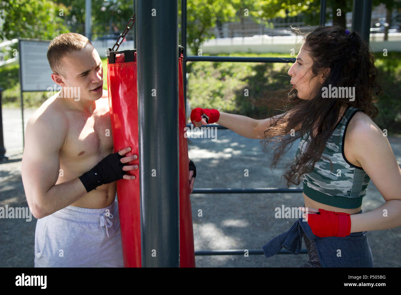 Muscular man holds punching bag to young woman engaged in boxing in summer park - Stock Image