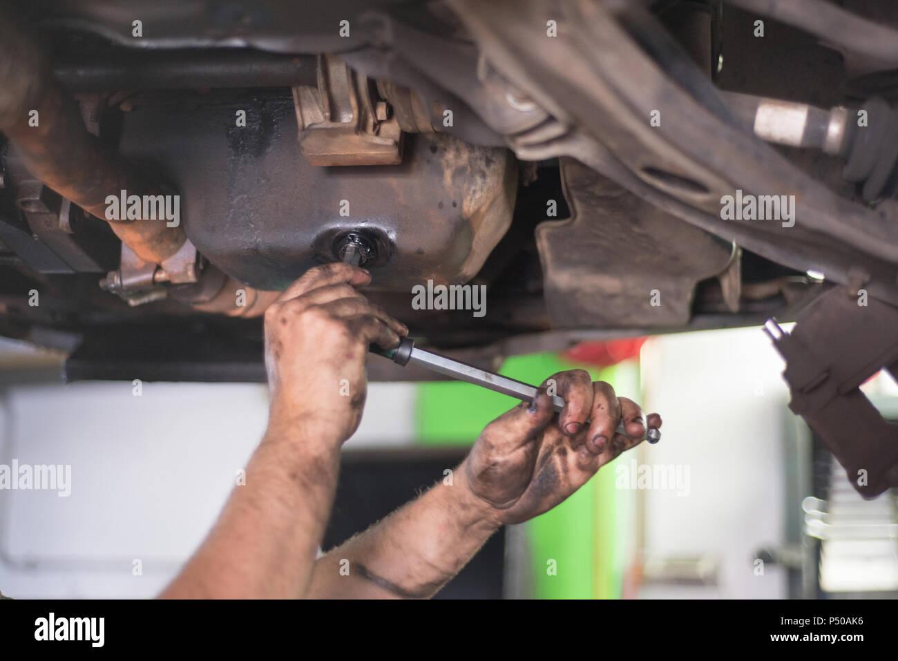 Car mechanic removing used engine oil - Stock Image