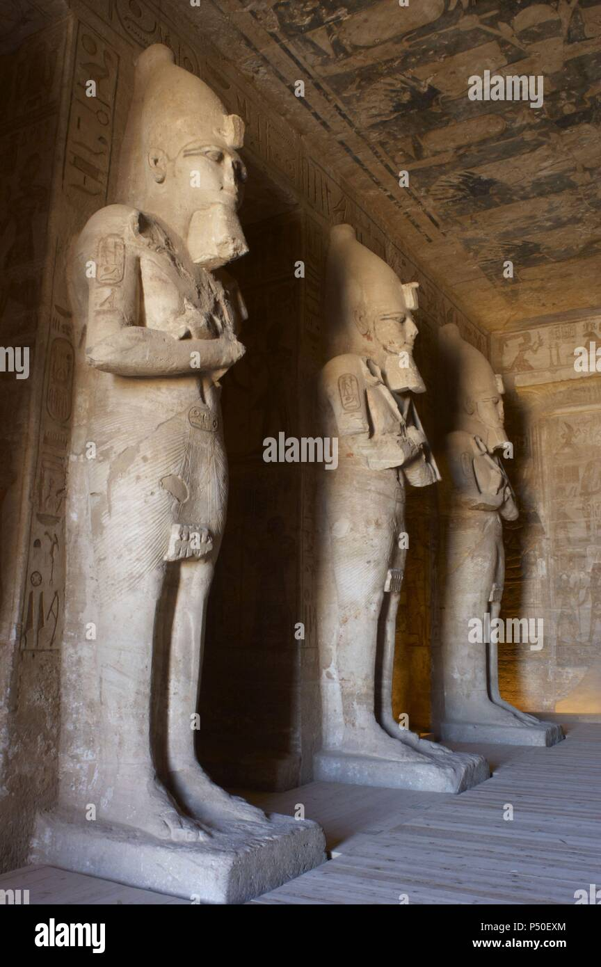 Egyptian art. Great Temple of Ramses II (1290-1224 BC). Funerary temple carved in the rock. View from inside the first room, with three of the eight statues of Ramses II as the god Osiris. Abu Simbel. Egypt. Stock Photo