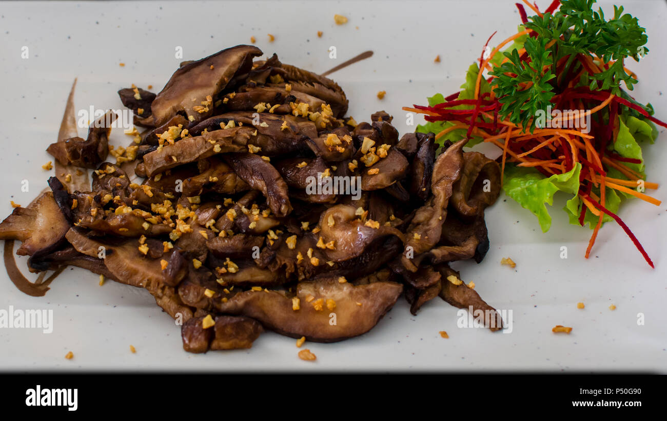 Fried sliced portabello mushrooms with garlic on white plate decorated with a smal salad - Stock Image