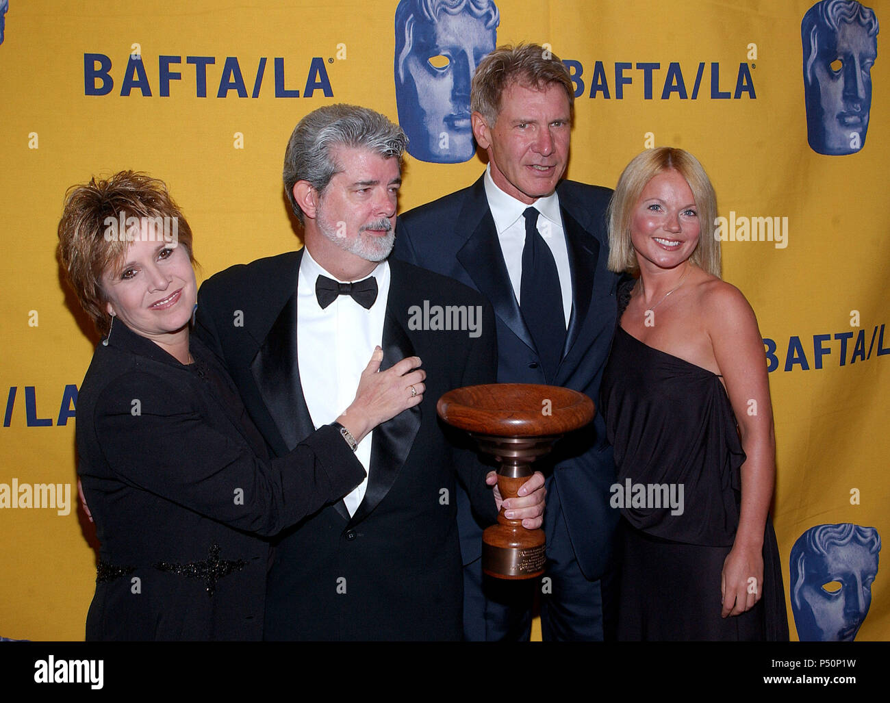 Carrie Fisher, Harrison Ford and the performer Geri Halliwell at The 11th Annual BAFTA-LA -Britannia Awards presented to George Lucas at the Beverly Hilton in Los Angeles. April 12,  2002.             -            FisherFordLucasHalliwell01.jpgFisherFordLucasHalliwell01  Event in Hollywood Life - California, Red Carpet Event, USA, Film Industry, Celebrities, Photography, Bestof, Arts Culture and Entertainment, Topix Celebrities fashion, Best of, Hollywood Life, Event in Hollywood Life - California,  backstage trophy, Awards show, movie celebrities, TV celebrities, Music celebrities, Topix, Bes - Stock Image