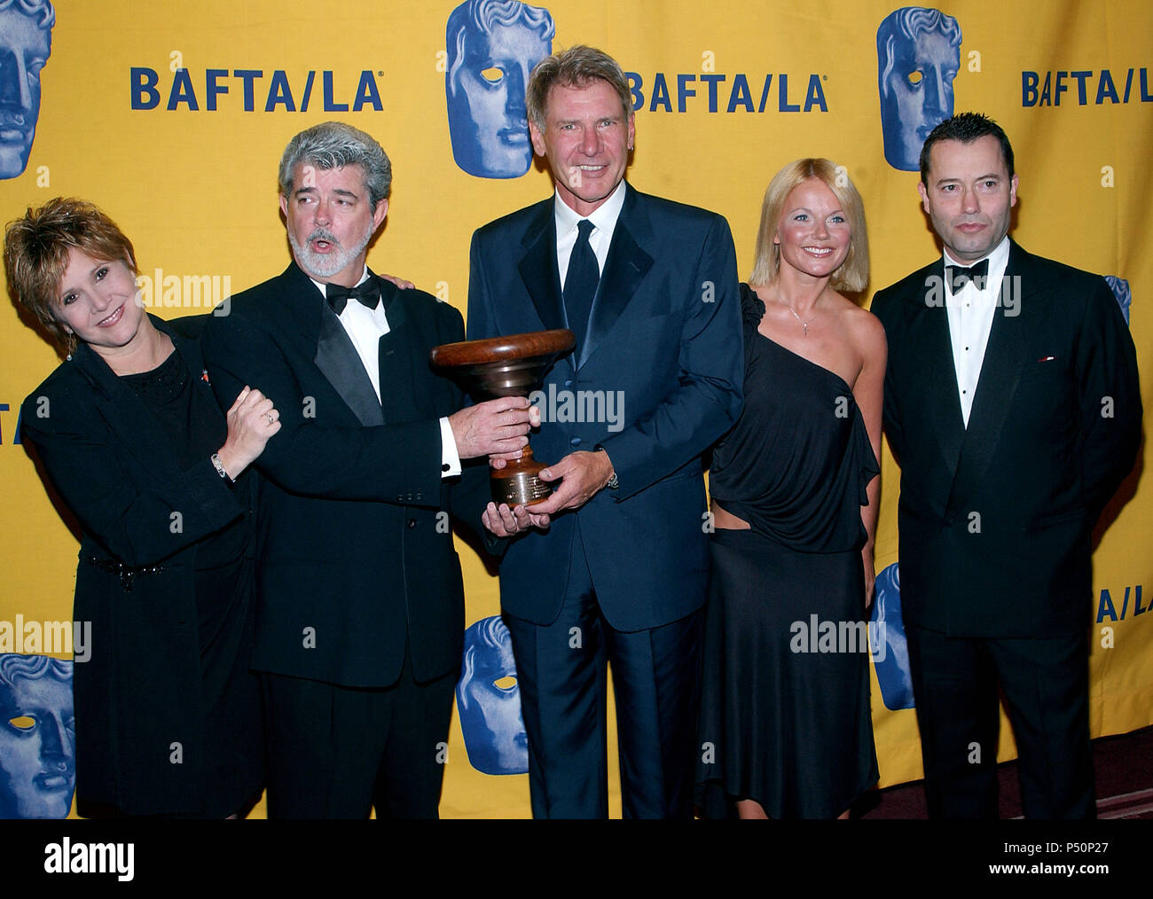 Carrie Fisher, Harrison Ford, Colin Callender (HBO film president) and the performer Geri Halliwell at The 11th Annual BAFTA-LA -Britannia Awards presented to George Lucas at the Beverly Hilton in Los Angeles. April 12,  2002.             -            FisherFordLucasHalliwell03.jpgFisherFordLucasHalliwell03  Event in Hollywood Life - California, Red Carpet Event, USA, Film Industry, Celebrities, Photography, Bestof, Arts Culture and Entertainment, Topix Celebrities fashion, Best of, Hollywood Life, Event in Hollywood Life - California,  backstage trophy, Awards show, movie celebrities, TV cele - Stock Image