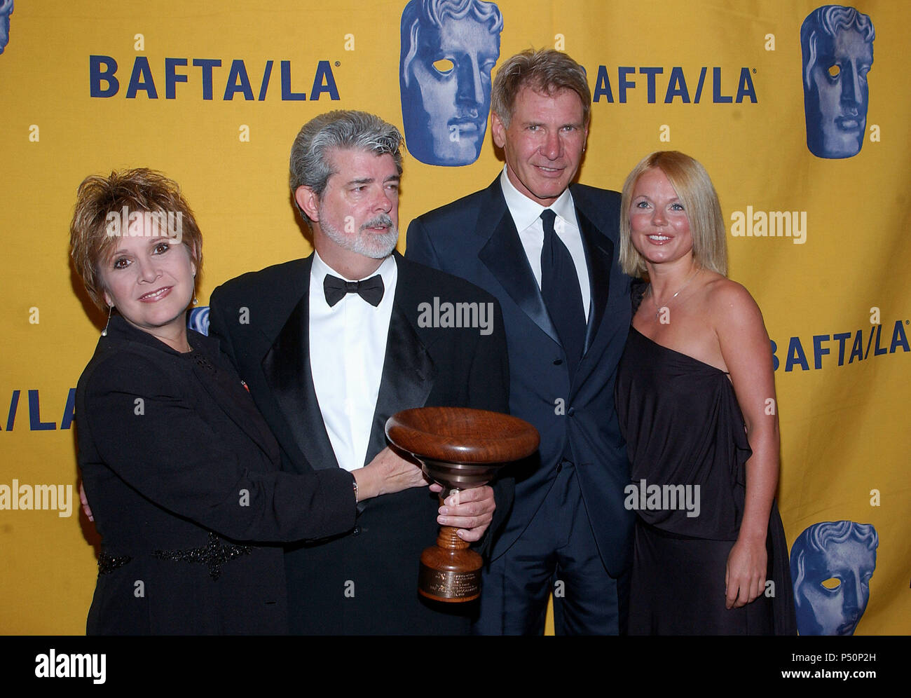 Carrie Fisher, Harrison Ford and the performer Geri Halliwell at The 11th Annual BAFTA-LA -Britannia Awards presented to George Lucas at the Beverly Hilton in Los Angeles. April 12,  2002.             -            FisherLucasFordHalliwell10.jpgFisherLucasFordHalliwell10  Event in Hollywood Life - California, Red Carpet Event, USA, Film Industry, Celebrities, Photography, Bestof, Arts Culture and Entertainment, Topix Celebrities fashion, Best of, Hollywood Life, Event in Hollywood Life - California,  backstage trophy, Awards show, movie celebrities, TV celebrities, Music celebrities, Topix, Bes - Stock Image