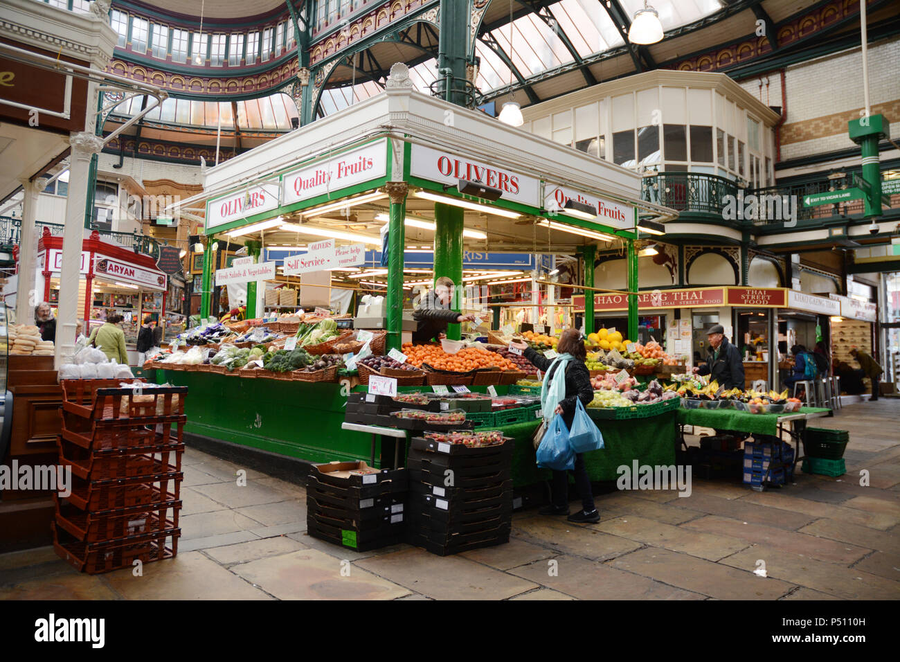 A shopper makes a purchase from a fruit and vegetable vendor at the indoor Kirkgate Market in the English city of Leeds, Yorkshire, United Kingdom. - Stock Image