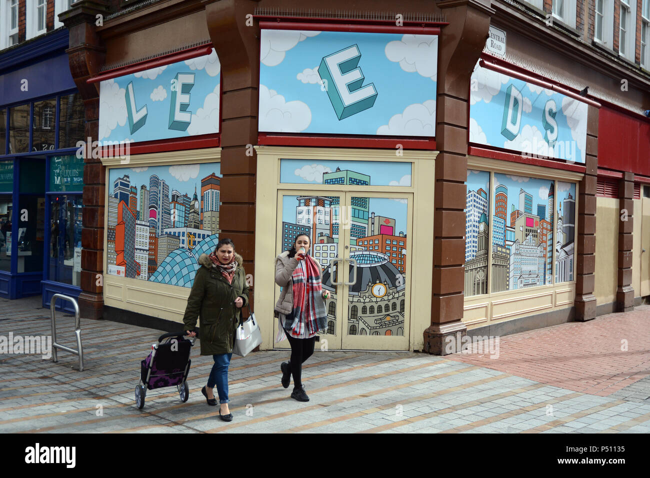 Two young women walk past an empty storefront with a wallpaper illustration of the city of Leeds, in a pedestrian zone, Leeds England, United Kingdom. - Stock Image