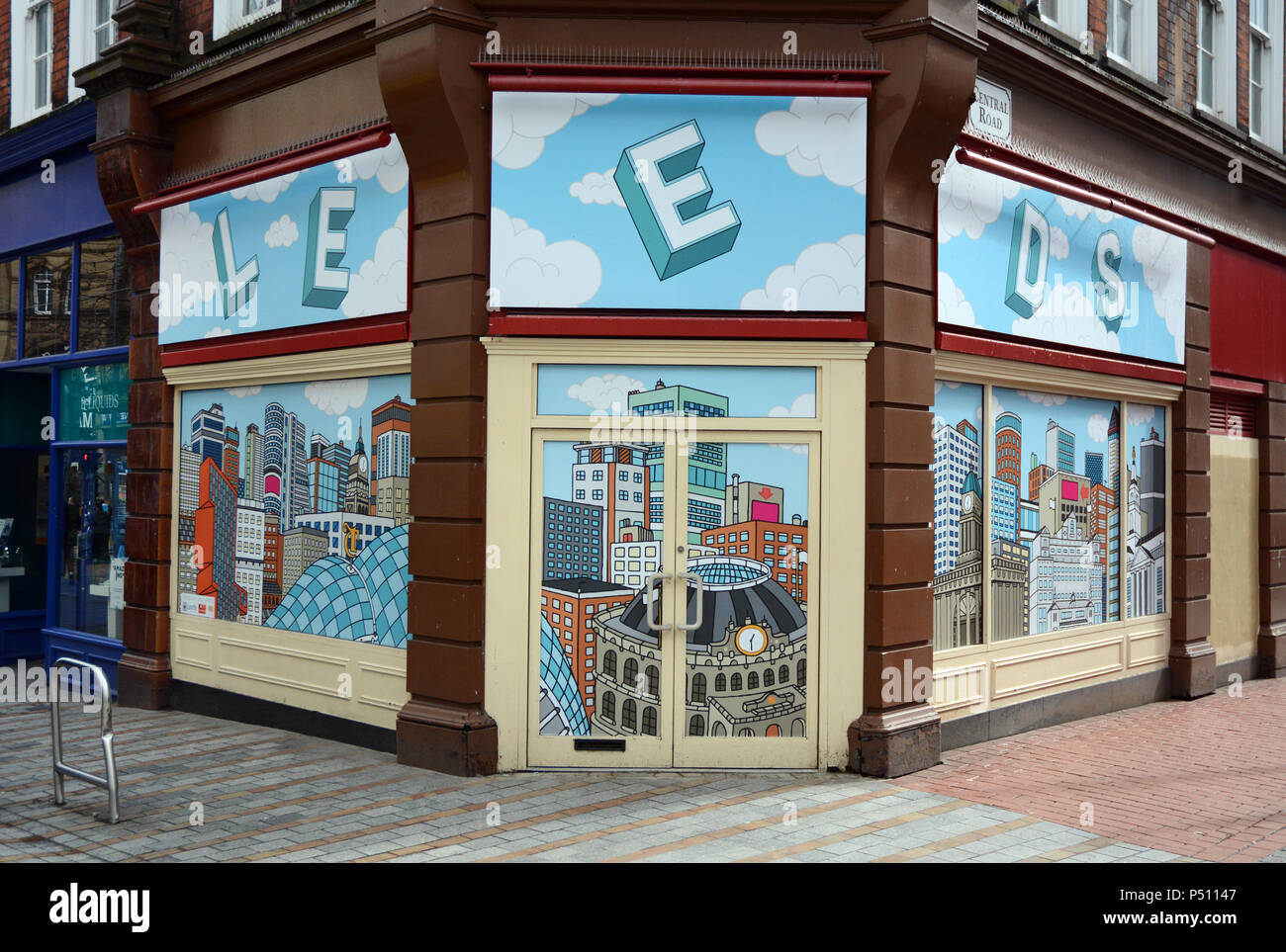 An empty storefront corner with a wallpaper illustration of the city of Leeds, in a pedestrian zone in Leeds England, United Kingdom. - Stock Image