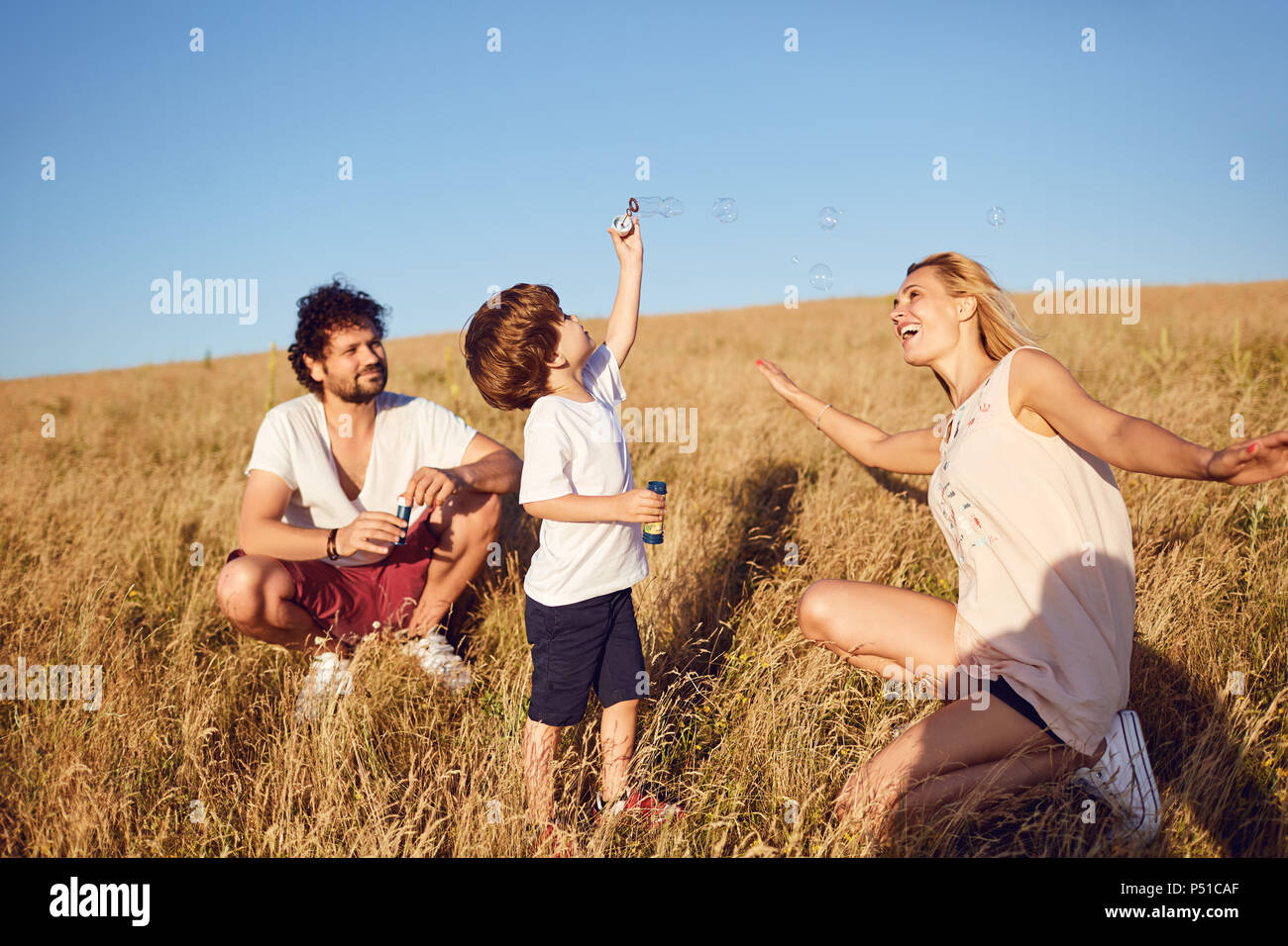 The family is playing with soap bubbles in nature - Stock Image