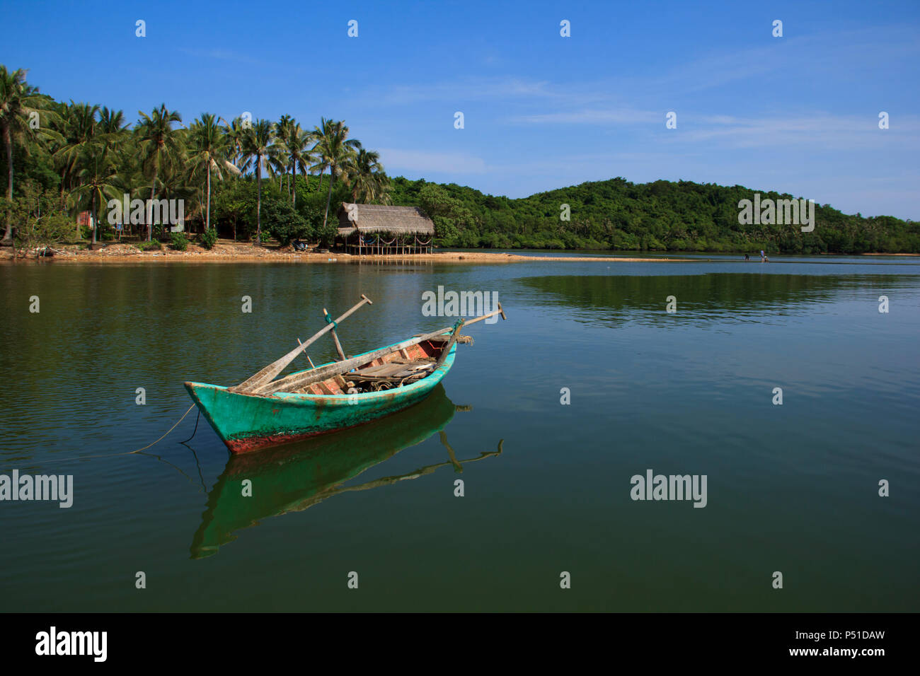 A single boat with reflection in jade water, at the tranquil island in Kien Giang, Vietnam - Stock Image