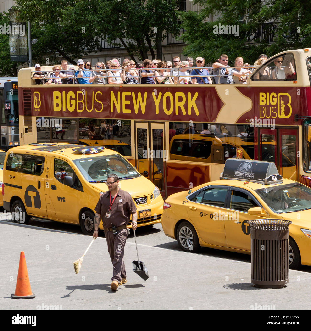 New york USA. Uniformed man from The MET with dustpan and brush sidewalk cleaning outside this famous museum watched bus load of tourists. - Stock Image