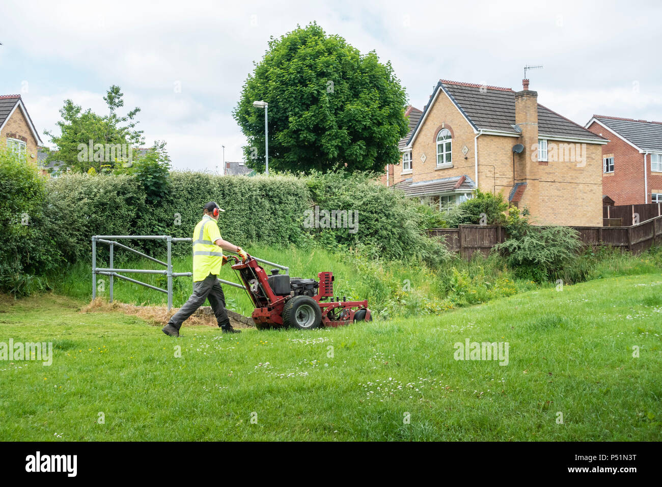 Gardener wearing Hi-Vis jacket mowing grass on a housing estate. - Stock Image