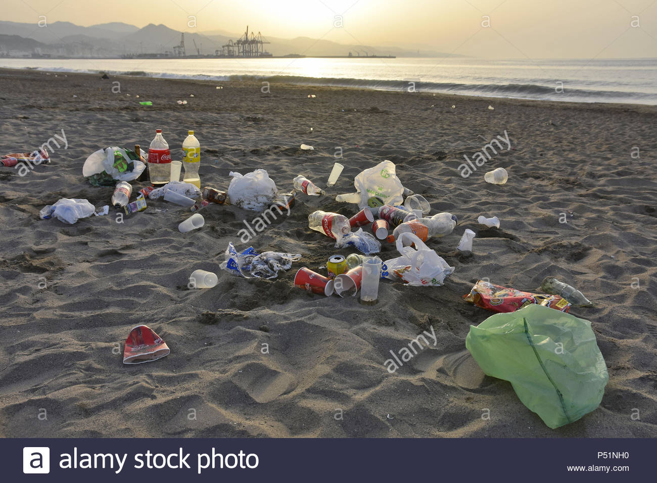 Rubbish left on the beach of Malaga after night party, industrial port in background, Andalusia Southern Spain Europe. - Stock Image