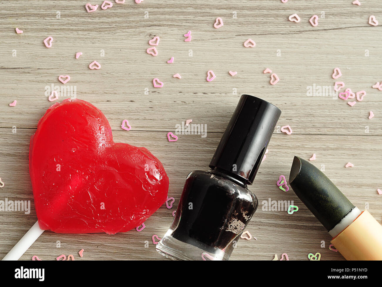 Black nail polish and lipstick displayed with a red heart shape ...