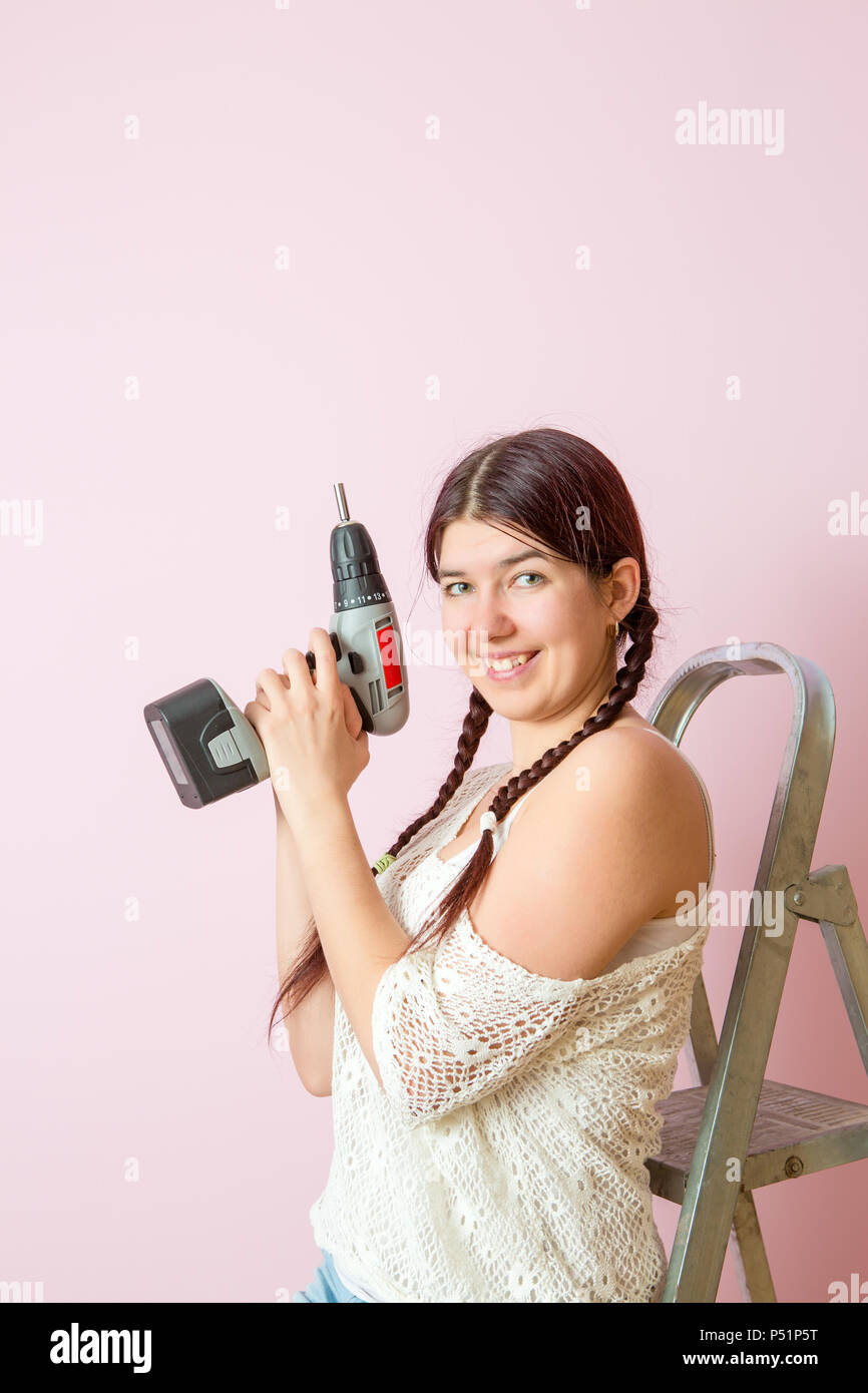 Photo of happy woman with drill near ladders - Stock Image