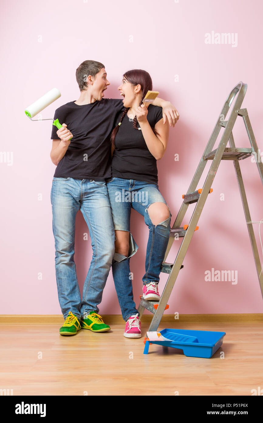Photo of woman and man with brush standing on stepladder Stock Photo