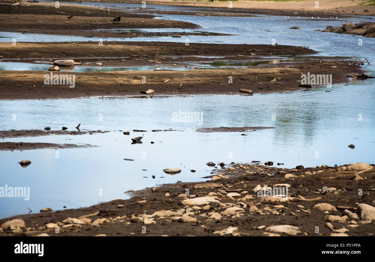 The river is shallow and very polluted by people. There is a lot of garbage and waste in the pond and this has become a huge problem. In the river, ev - Stock Image