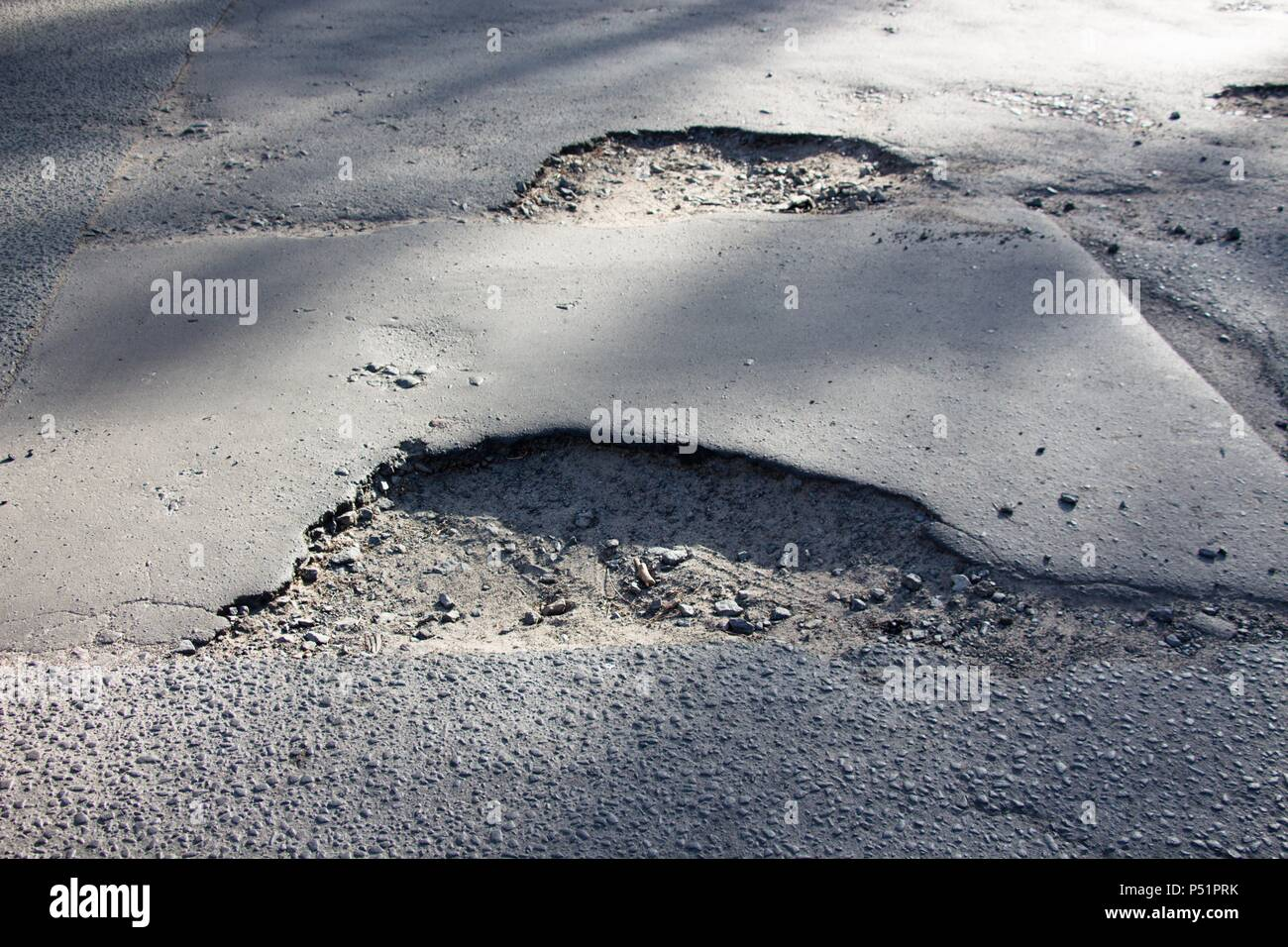 Pits that have arisen on the road surface and are not repaired. Problem in irresponsibility and non-compliance with requirements. Ignoring the repair - Stock Image