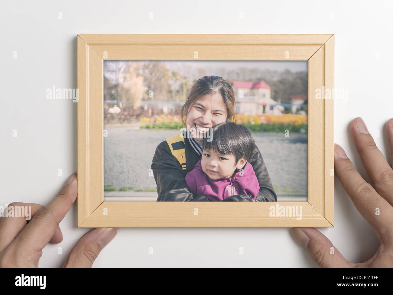 Daddy Hand Holding A Picture Of Mother And Son In Frame Stock Photo