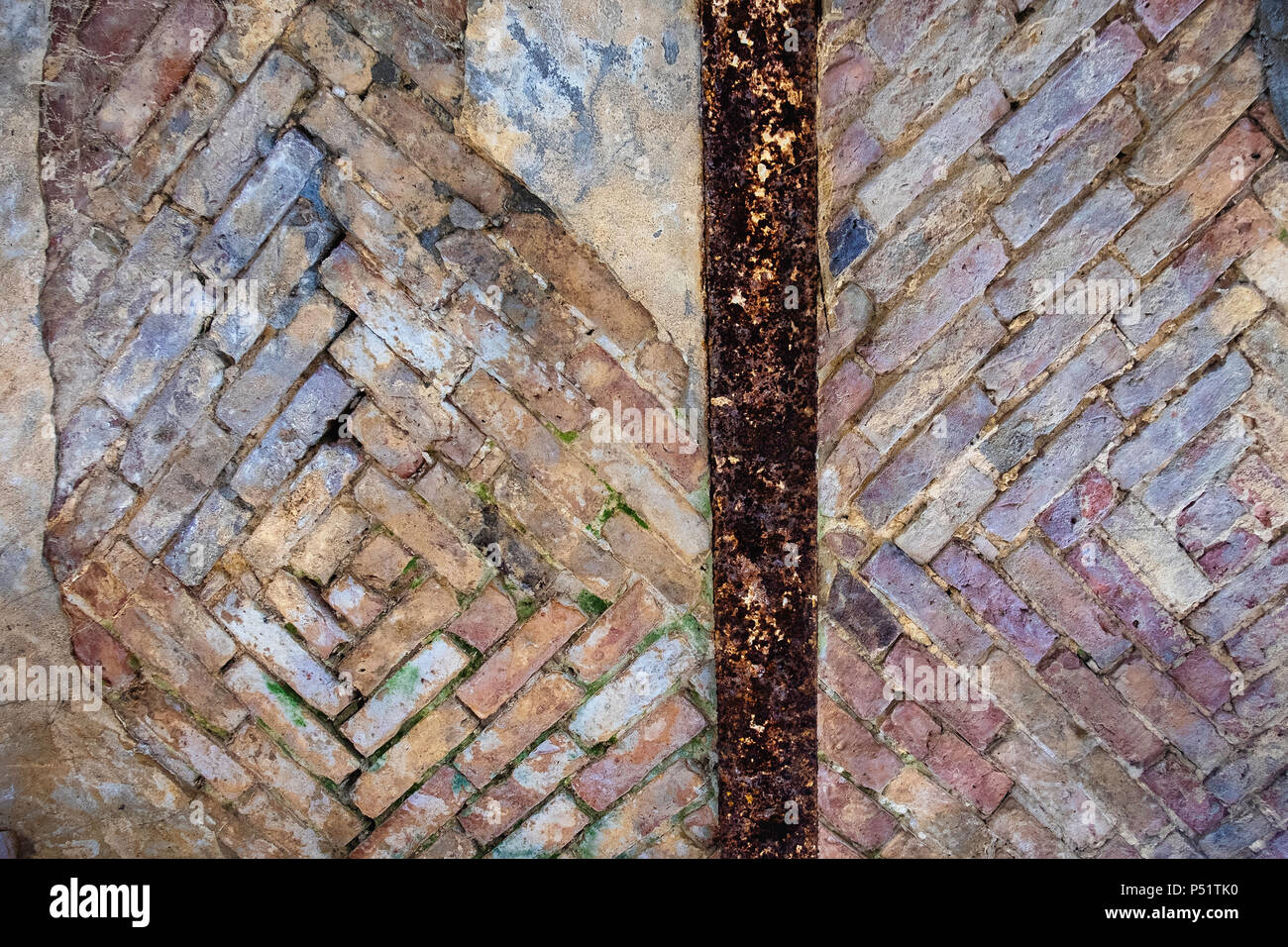 Urban Decay. Dilapidated old building detail, weather old brick wall with rusty irom beam. Brick pattern - Stock Image
