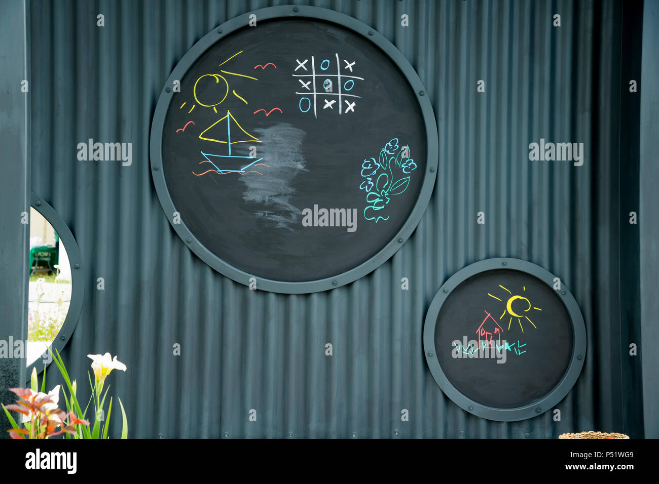Close-up of circular blackboards in garden play area - CCLA : A Family Garden, RHS Chatsworth Flower Show, Chatsworth House, Derbyshire, England, UK. - Stock Image