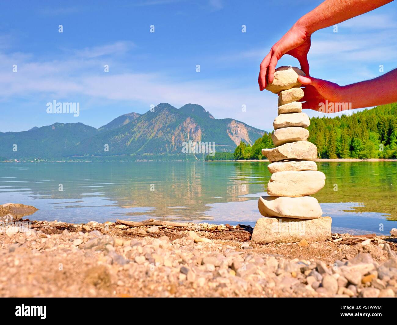 Pyramid of flat stones on a pebbly lake beach, the mountains mirroring in smooth water level. - Stock Image