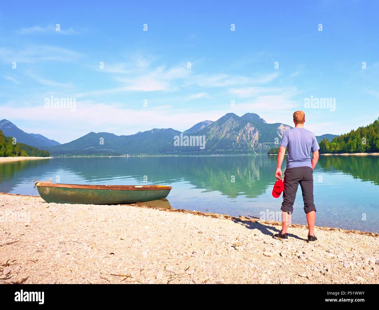 Adult man in blue shirt at old fishing paddle boat at mountains lake coast. Sunny spring day. - Stock Image