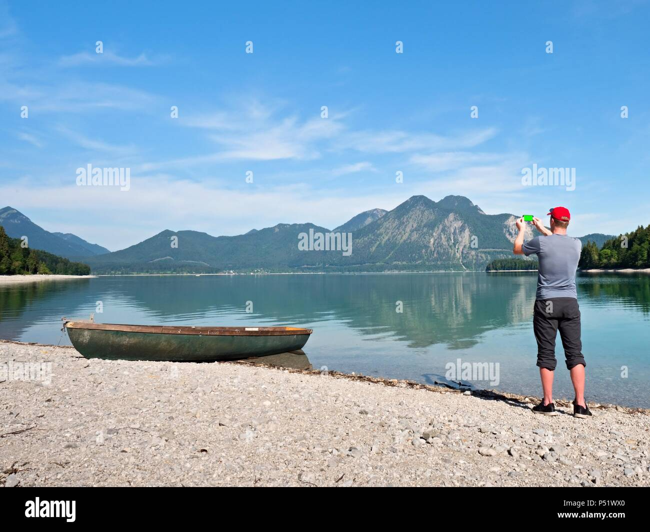 Photographer with eye at viewfinder is taking photo of lake with Alps mountains in background. Artist works. - Stock Image