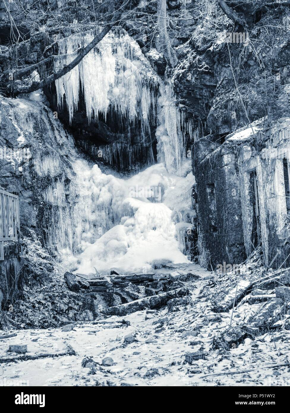 Frozen waterfall between rocks. Fallen icicle bellow waterfall, stony and mossy stream bank. Stock Photo