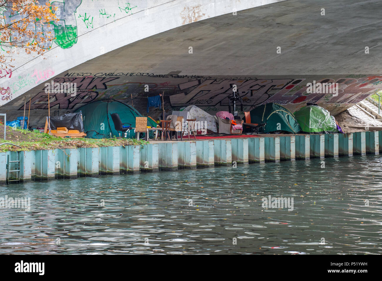 Tents of homeless people under a canal bridge at Berlin Westhafen Stock Photo