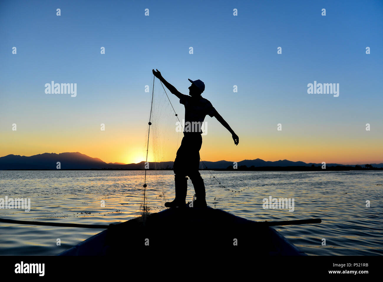silhouette of man fishing - Stock Image