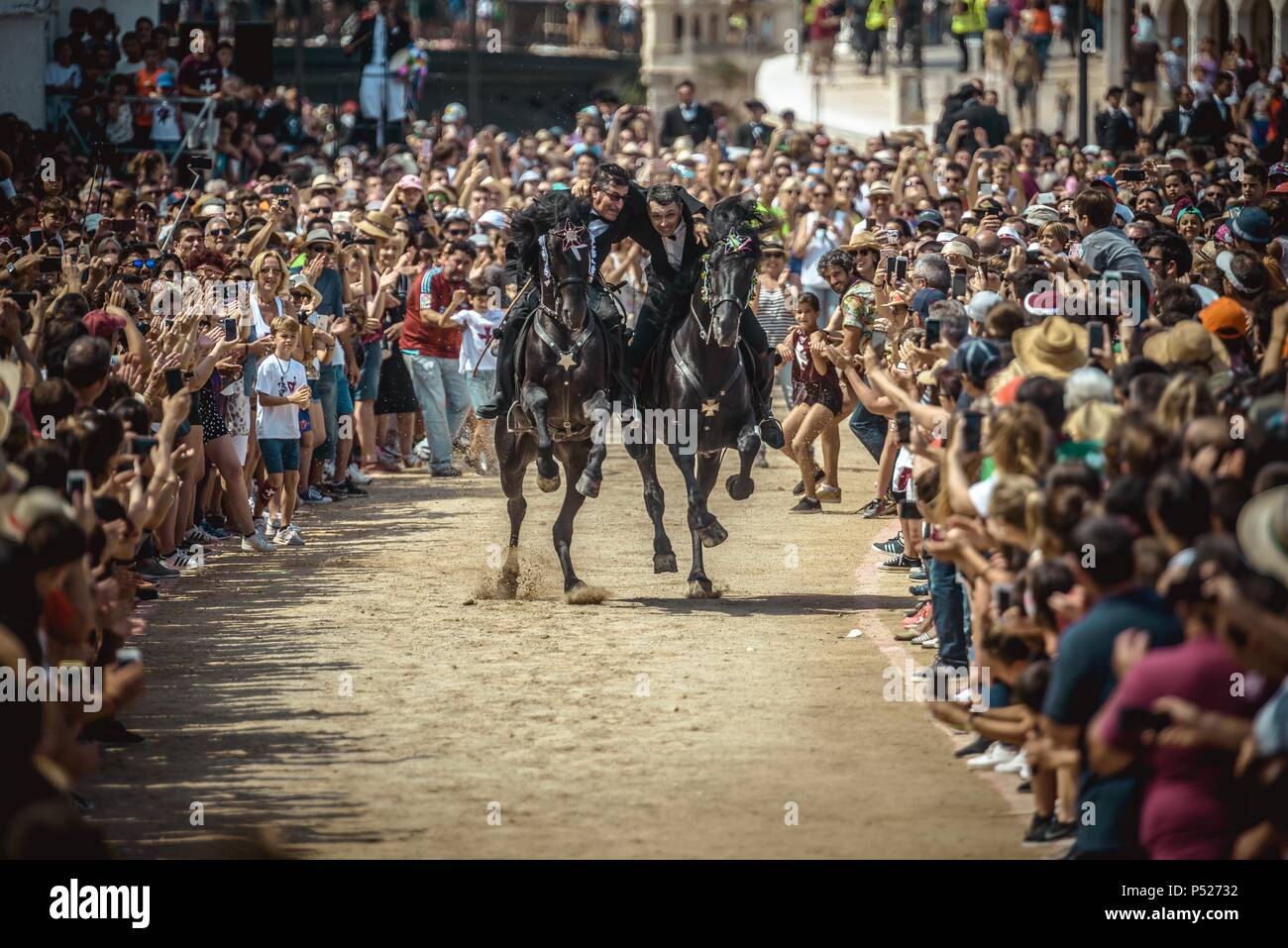 Ciutadella, Spain. 24 June, 2018:  Two 'caixers' (horse riders) gallop together with their arms entwined during the training session for the 'Jocs des Pla' (medieval tournament) during the traditional 'Sant Joan' (Saint John) festival in Ciutadella de Menorca Credit: Matthias Oesterle/Alamy Live News - Stock Image