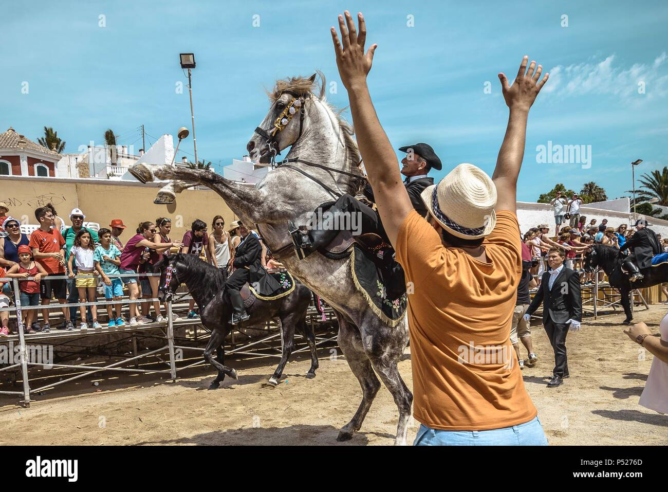 Ciutadella, Spain. 24 June, 2018:  A 'caixer' (horse rider) rears up on his horse surrounded by a cheering crowd at the end of the training for the 'Jocs des Pla' (medieval tournament) during the traditional 'Sant Joan' (Saint John) festival in Ciutadella de Menorca Credit: Matthias Oesterle/Alamy Live News - Stock Image