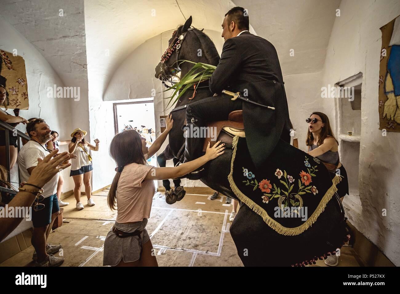 Ciutadella, Spain. 24 June, 2018:  A 'caixer' (horse rider) rears up on his horse in a private house during the 'Caragol de Santa Clara' during the traditional 'Sant Joan' (Saint John) festival in Ciutadella de Menorca Credit: Matthias Oesterle/Alamy Live News - Stock Image