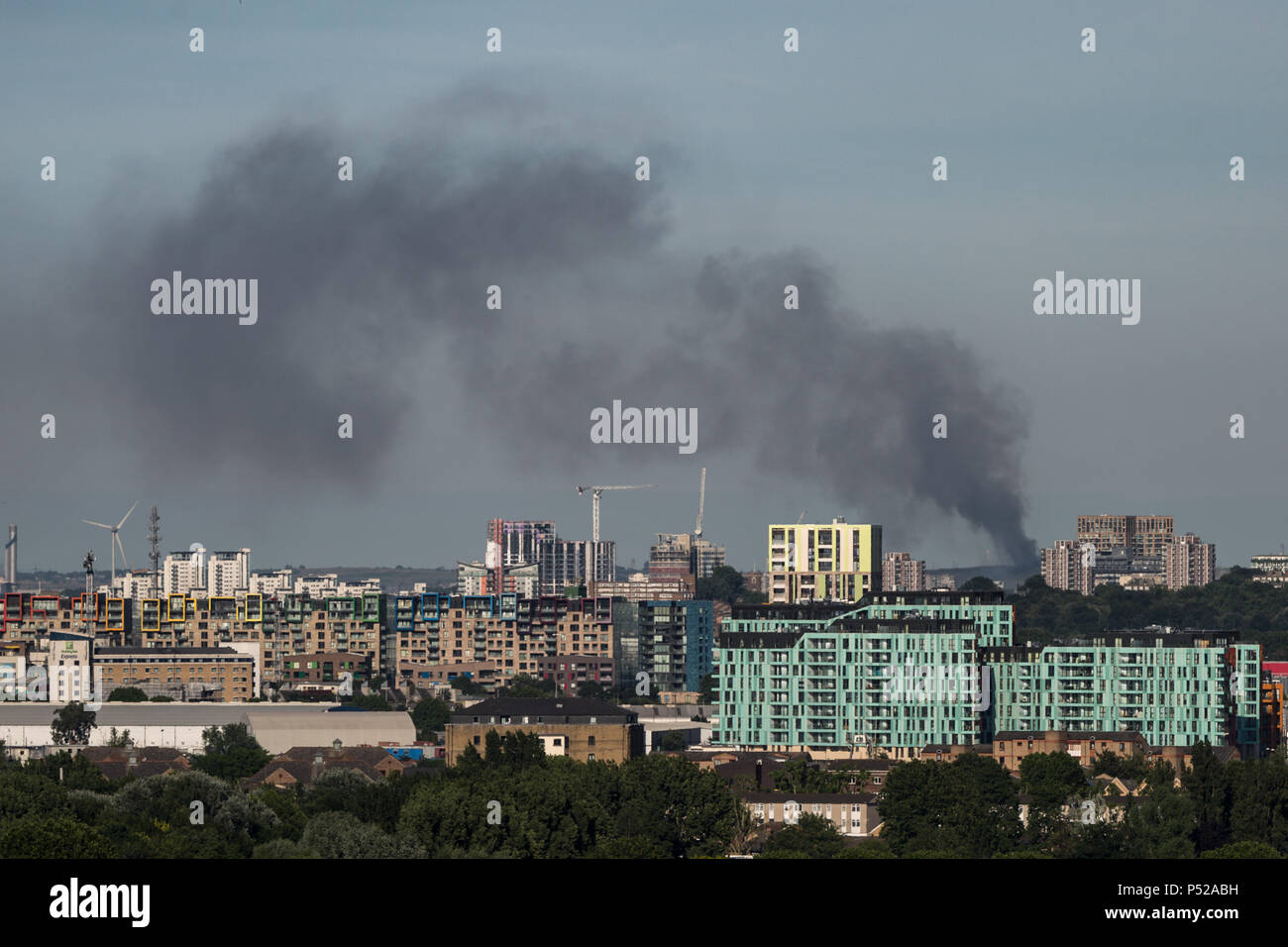 London, UK. 24th June, 2018. London Fire: Black smoke rises from a landfill site fire in Rainham, east London with two hectares alight. Ten fire engines, 72 firefighters and officers are present at the landfill site in Coldharbour Lane, Rainham this afternoon. The Brigade was called at 1355 and firefighters are likely to remain at the scene throughout the evening. The cause of the fire is not known at this stage. Credit: Guy Corbishley/Alamy Live News Stock Photo
