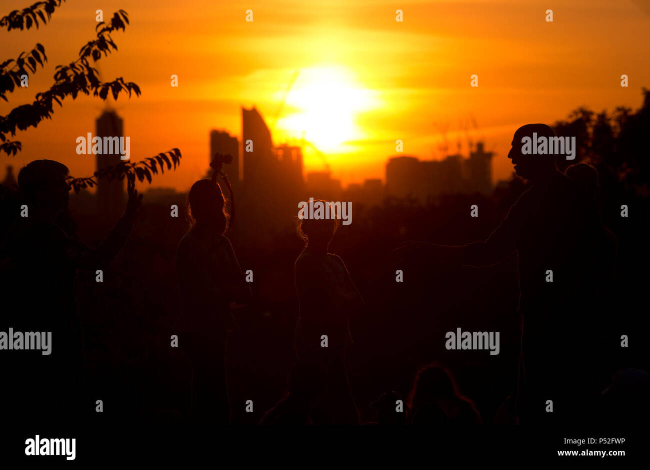 London, UK. 24th June, 2018. People look at the sun setting over the city of London from Telegraph Hill, south London, in a hot evening as the weather reached temperatures over 25C in the UK today on Sunday June 24, 2018.         Credit: Isabel Infantes/Alamy Live News Stock Photo