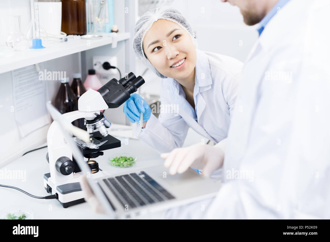 Scientists discussing data received from microscope research Stock Photo