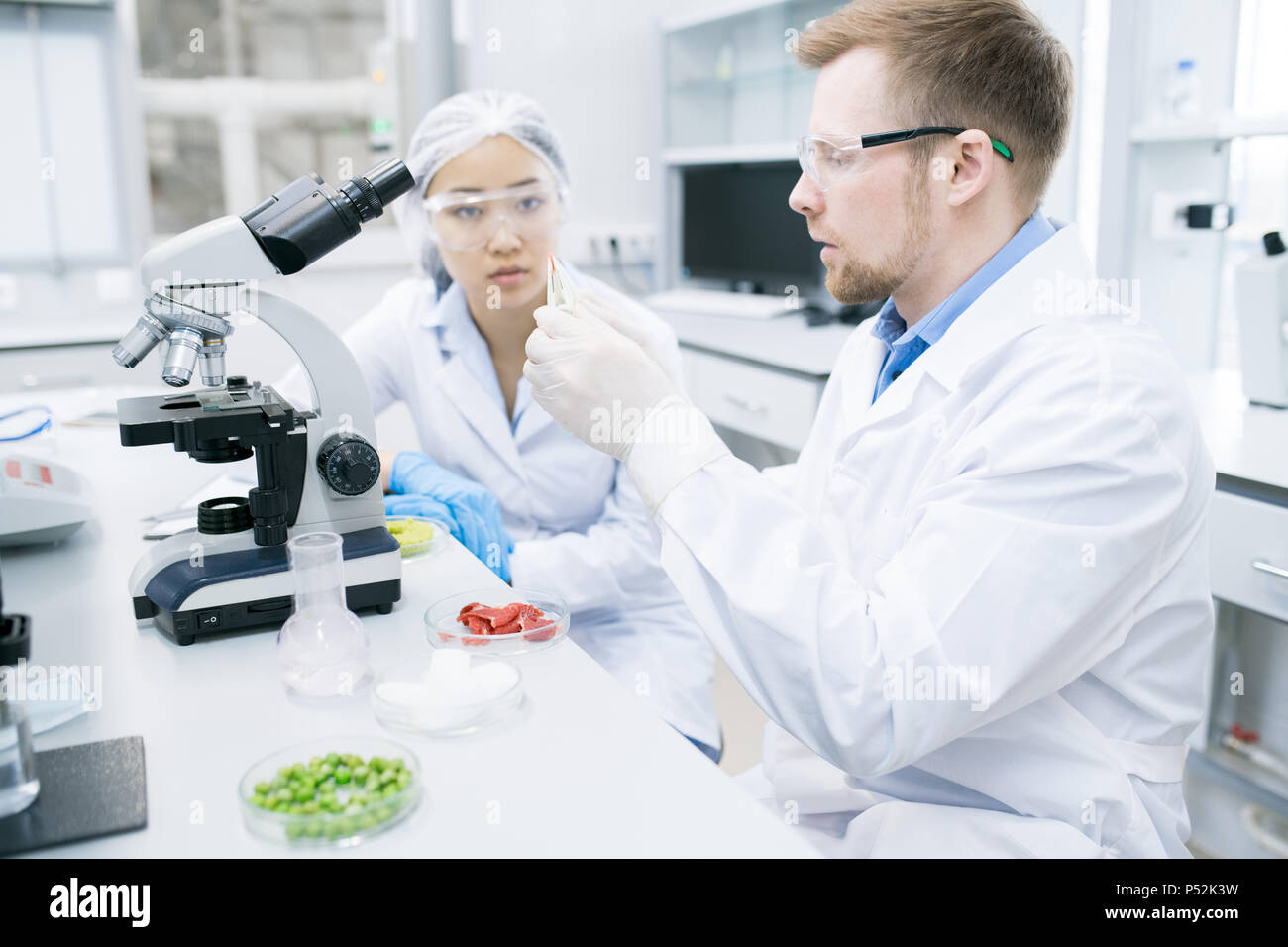 Woman scientist looking at colleague studying meat - Stock Image
