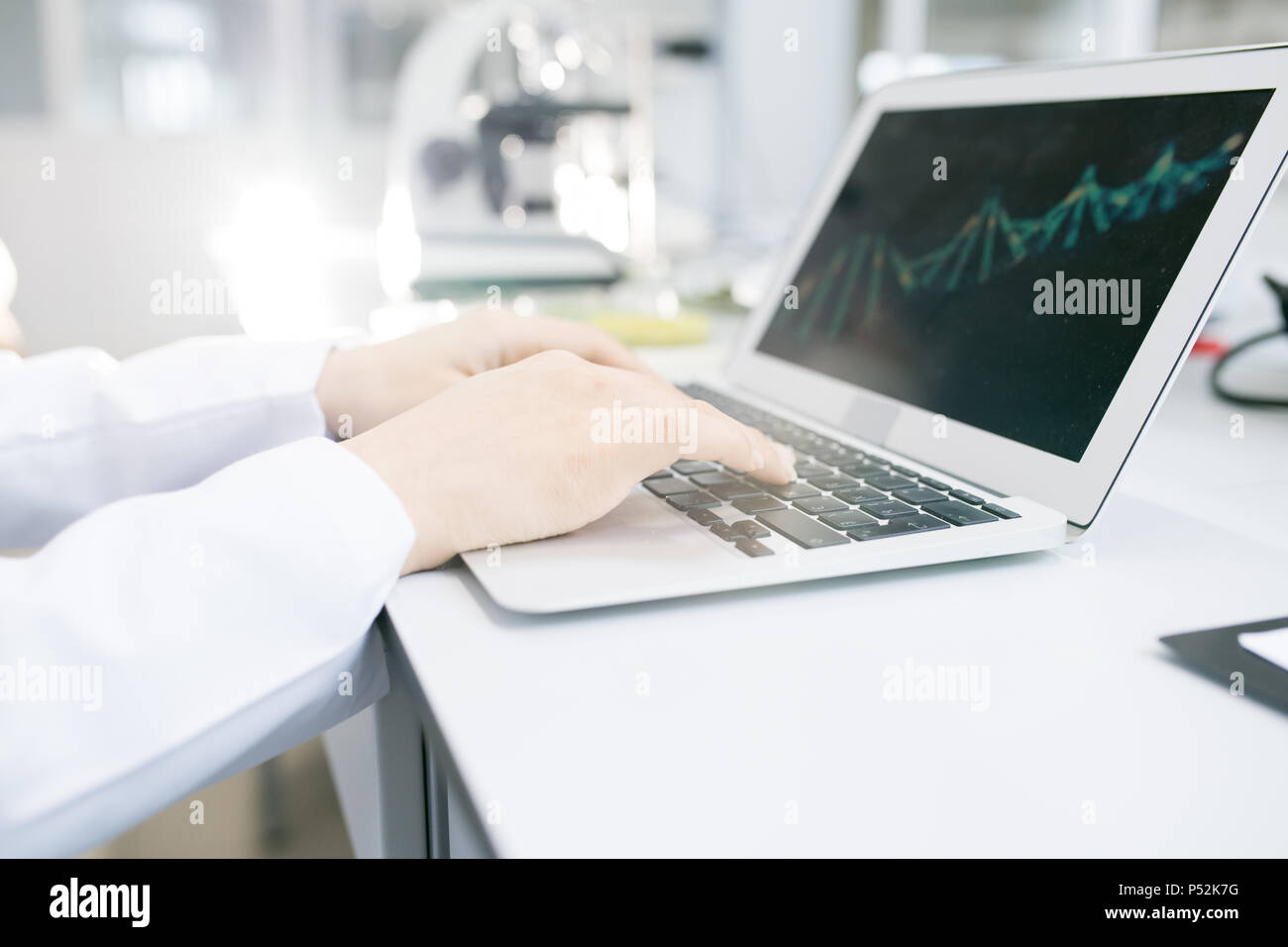 Scientist hands editing DNA model on laptop - Stock Image