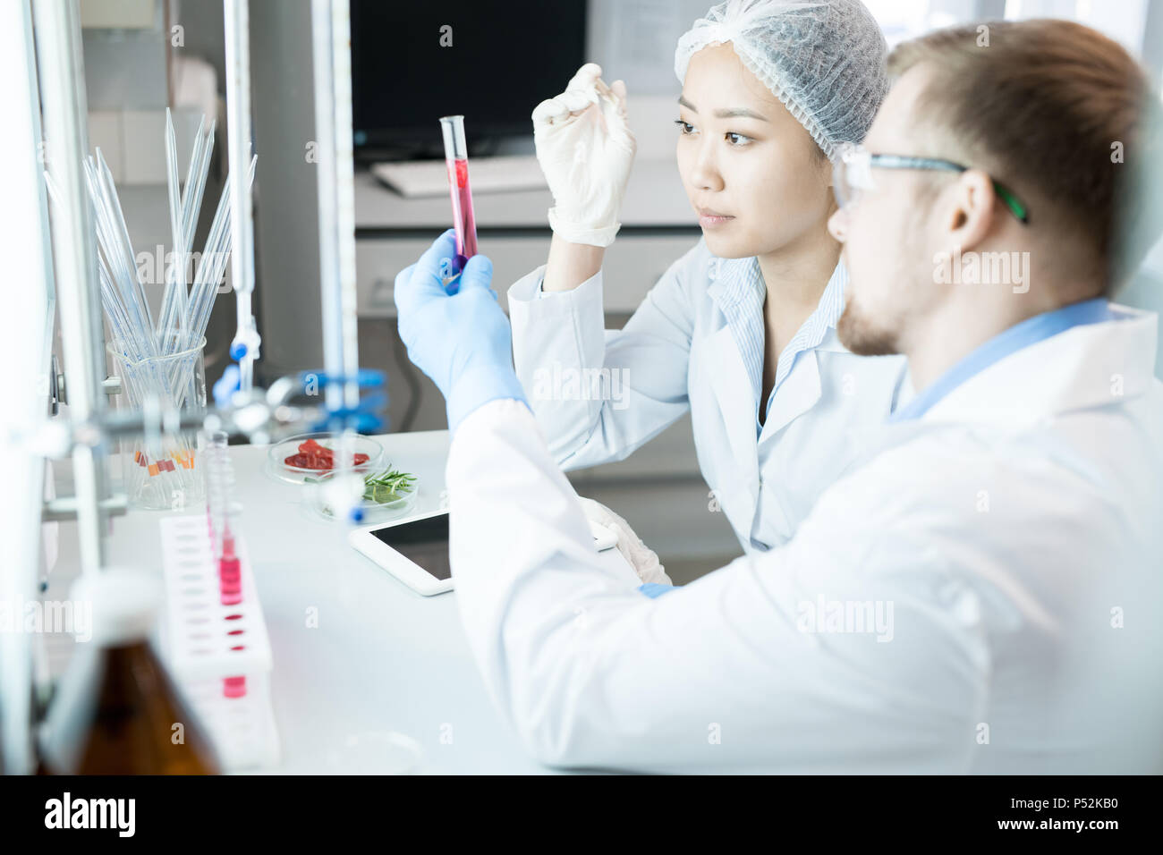 Microbiologists observing test glass with pink liquid - Stock Image